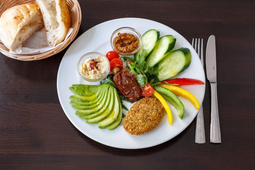 Veganes Frühstück hausgemachtes Hummus, Avocado, Kalamata-Oliven, Cherrytomaten, Paprika, Pesto, Gurken, Falafel, Pita Brot